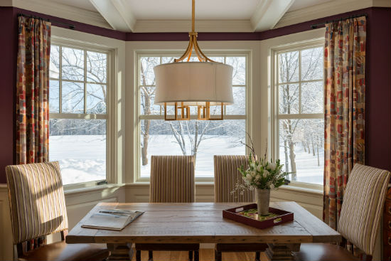 A table situated strategimcally before large windows provides a serene place to work on a snowy afternoon. source:  Karosis Photograhy