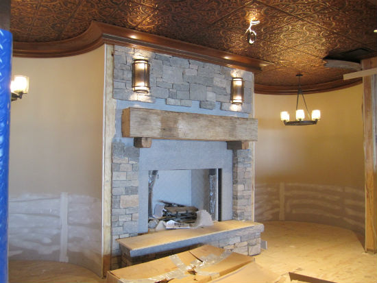 An inglenook in the dining room.  The mantle is made from a reclaimed barn beam from Maine.  The will eventual;ly be a circular banqueet flanking the fireplace. The ceiling is copper-colored tin.  Source:  TMS Architects