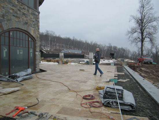 Clubhouse's west terrace with TMS principal, Shannon Alther, looking into the dining room.  Piers at the end are a part of a fence overlooking the pool area with the bocce ball course to the right. Source:  TMS Architects