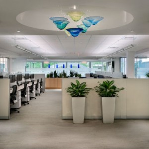 A view of the space from the front entrance. Blown glass light fixtures in various shapes and sizes are repeated throughout the space, lit from above and use Bottomline's branding color scheme. Source: Rob Karosis Photography
