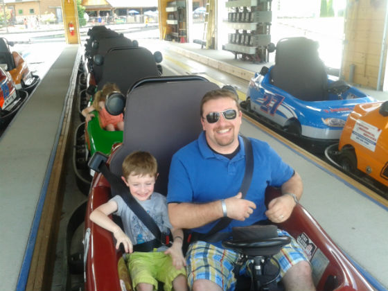 TMS Project Architect Tim Giguere and his son Logan enjoy a ride on a tandem go- kart.